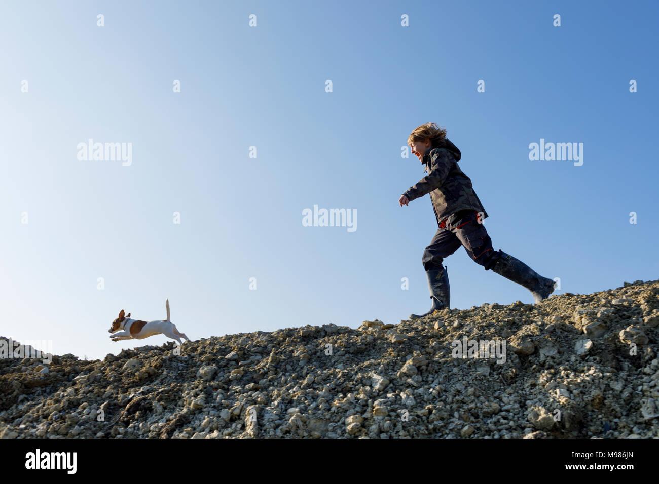 Muchacho feliz corriendo con el perro bajo un cielo azul Imagen De Stock