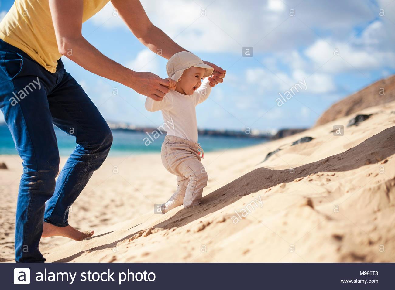 España, Lanzarote, niña caminando por la playa, con la ayuda de su padre. Imagen De Stock