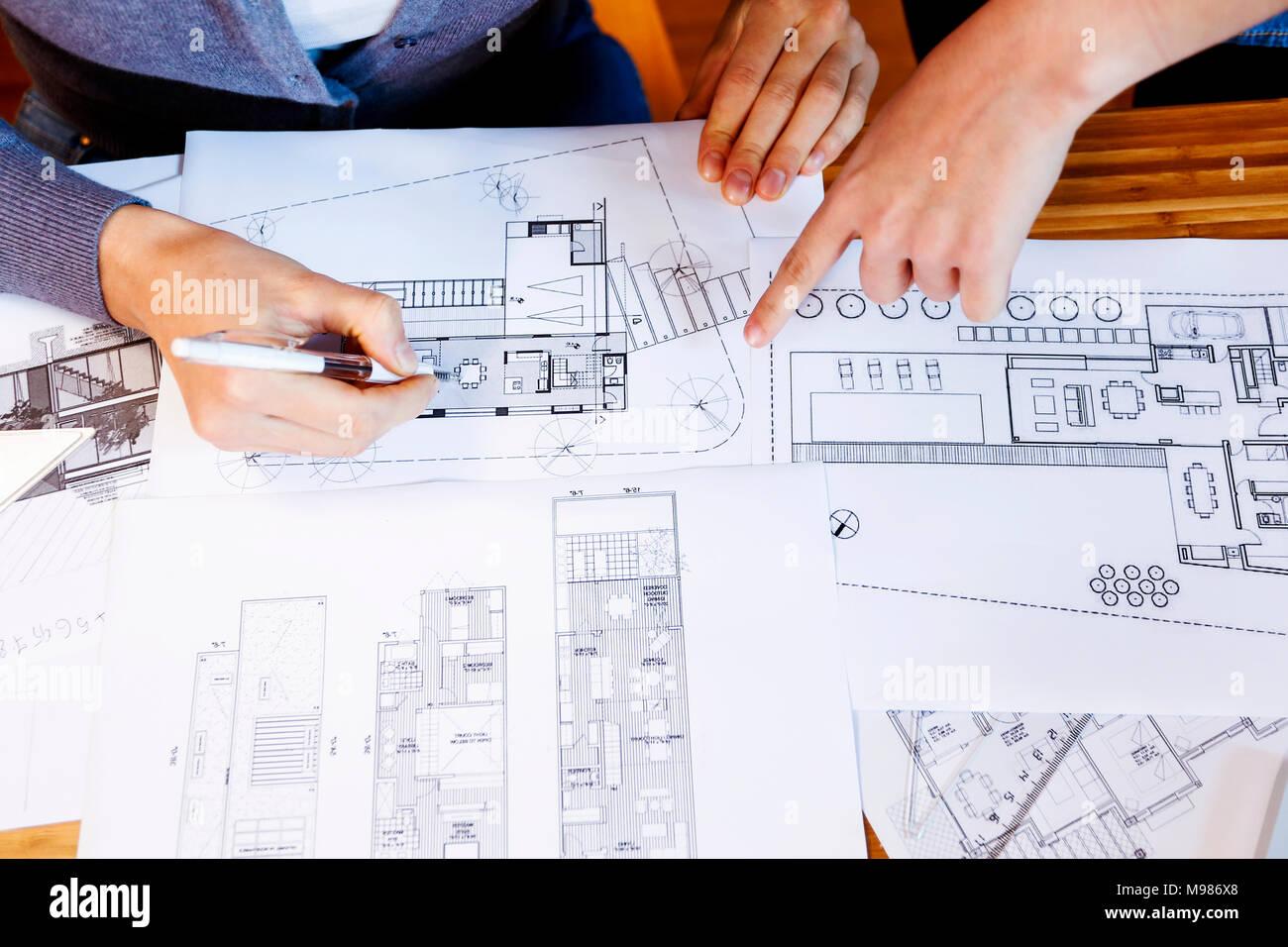 El equipo de arquitectos que trabajan en un proyecto, discutiendo blueprints Foto de stock