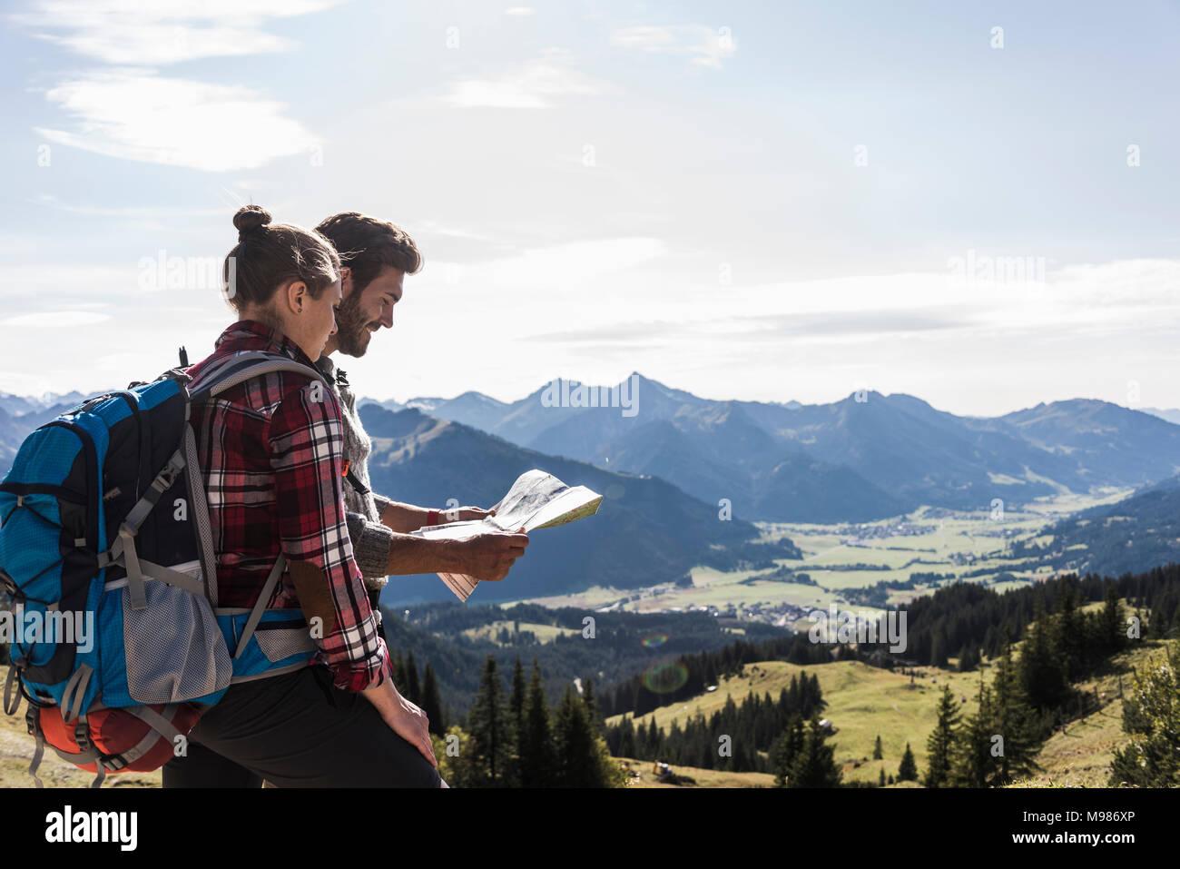 Austria, Tirol, la joven pareja mirando el mapa en mountainscape Imagen De Stock