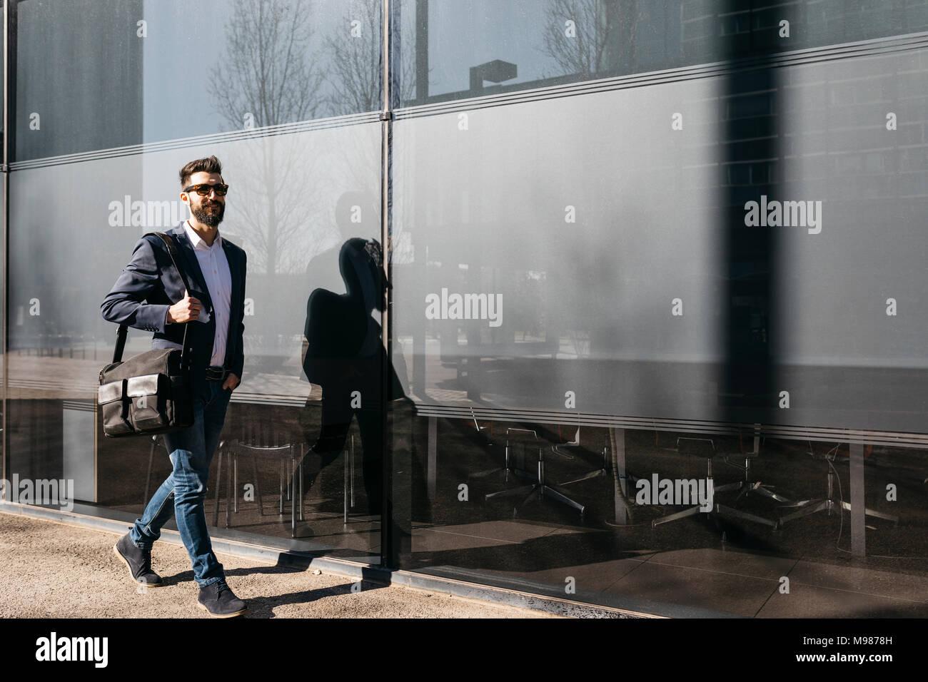 Empresario con gafas de sol caminando a lo largo de la construcción Imagen De Stock