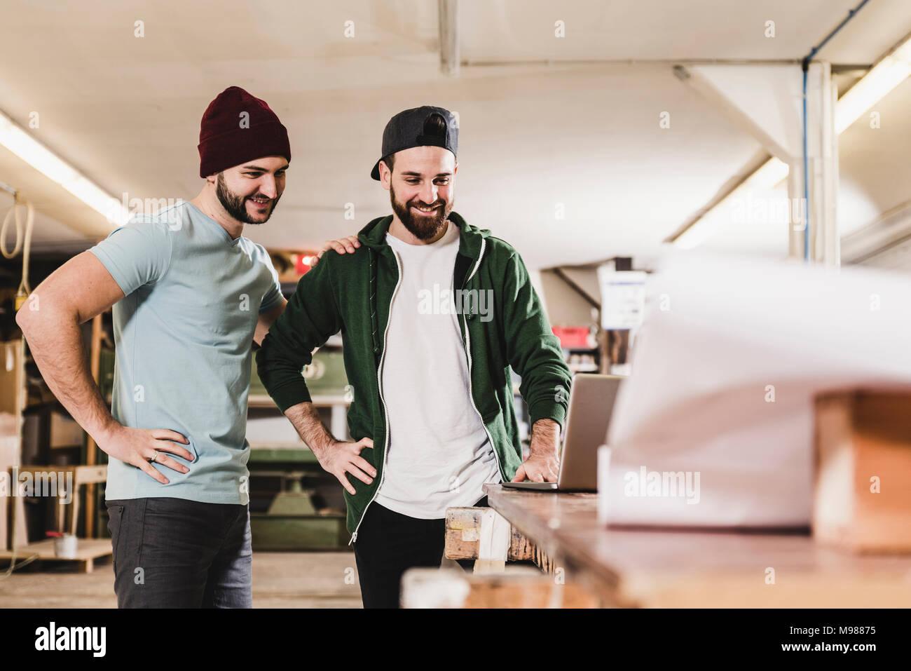Dos hombres jóvenes sonriendo mirando portátil en el taller Foto de stock