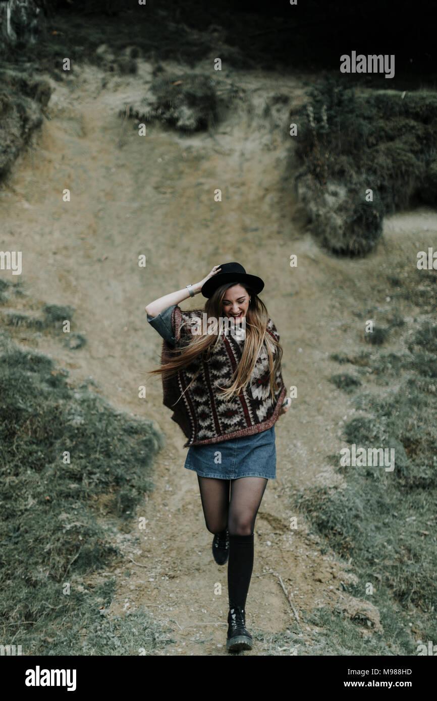 Moda joven vestidos de poncho y sombrero que ejecutan downhill Imagen De Stock