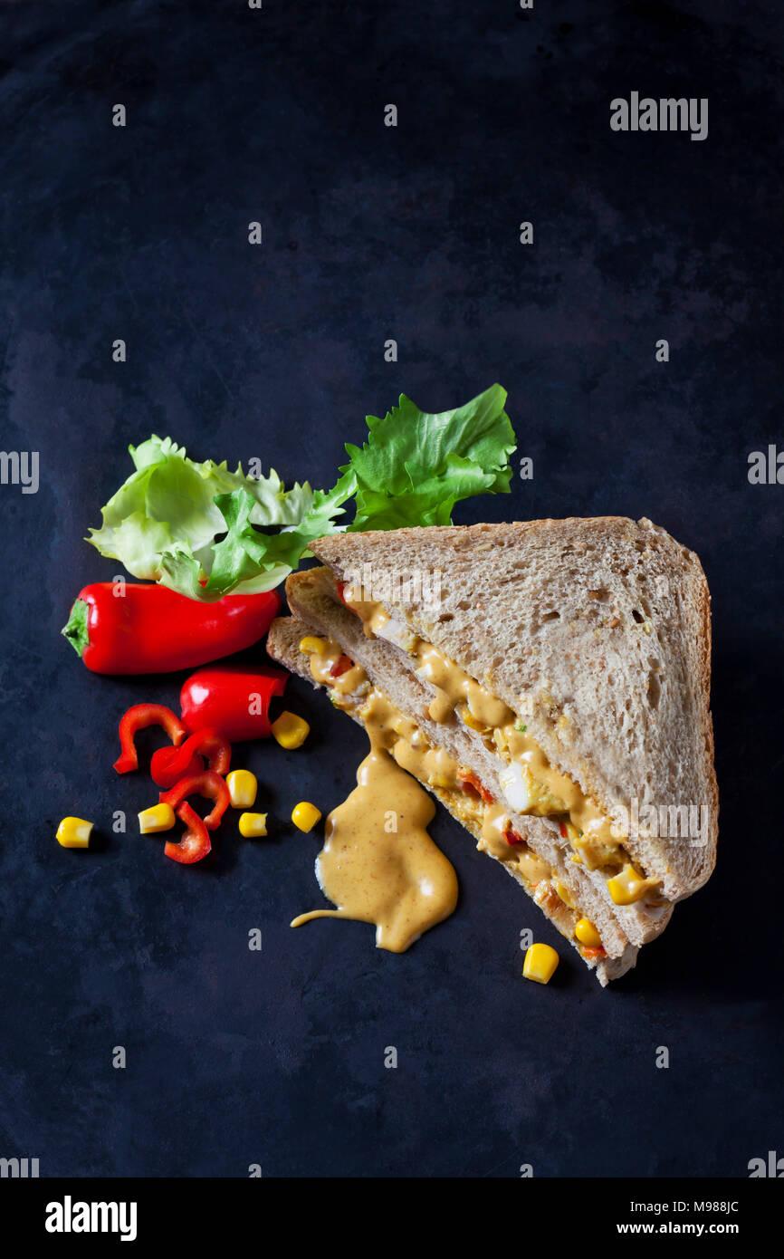 Sándwich de pollo con maíz, pepperoni y salsa de curry sobre suelo oscuro Imagen De Stock