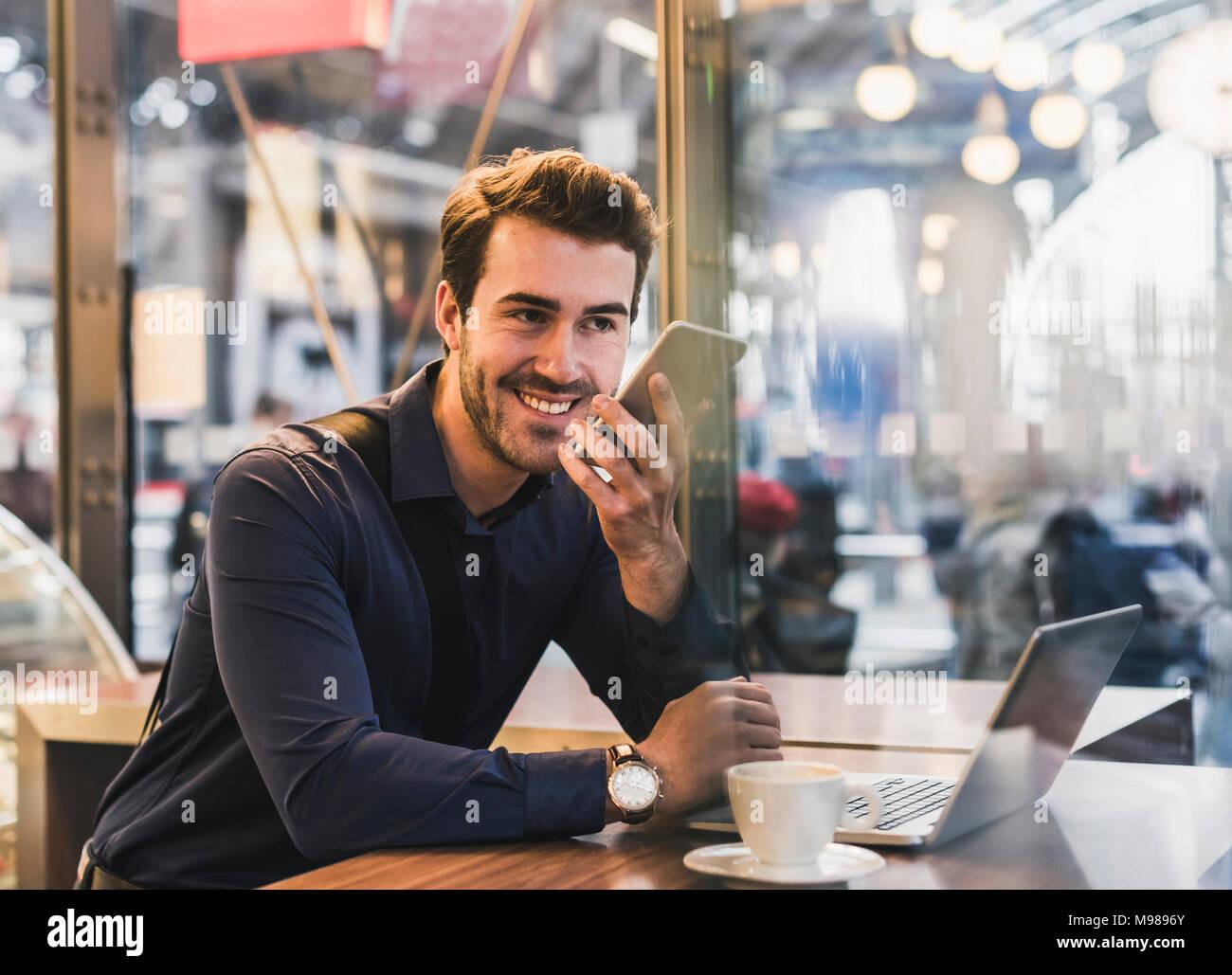 Sonriente joven empresario en un café en la estación de tren con teléfono móvil y portátil Imagen De Stock