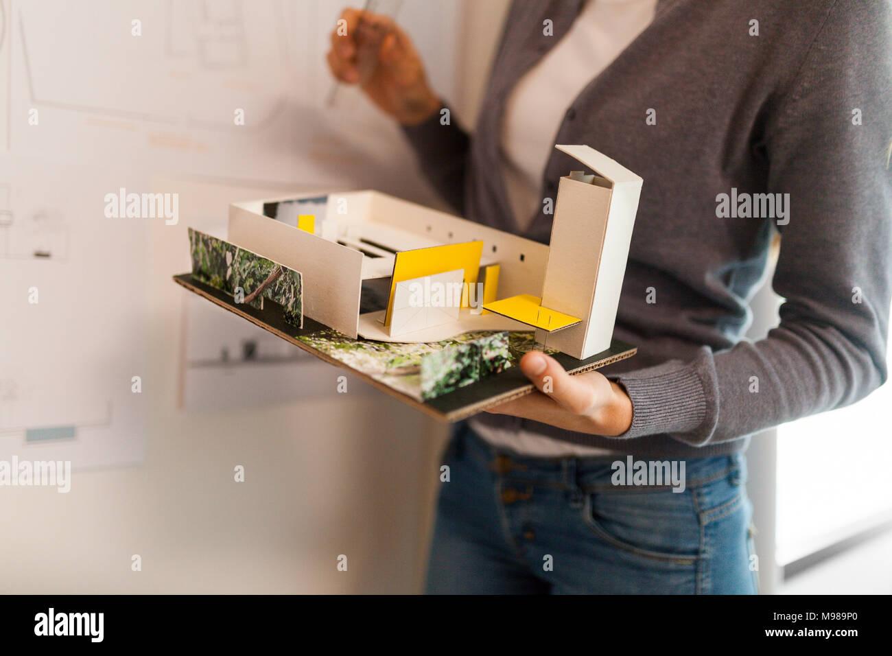 Mujer trabajando en un proyecto de arquitecto, sosteniendo el modelo arquitectónico Imagen De Stock