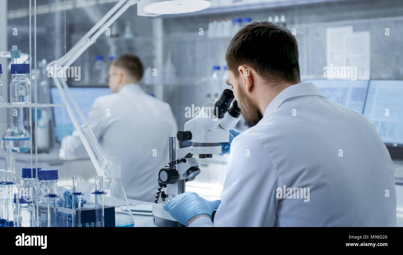 Foto de Investigador ajusta su microscopio. Él trabaja en un moderno laboratorio de gama alta con vasos de precipitados, cristalería, microscopio y monitores Imagen De Stock