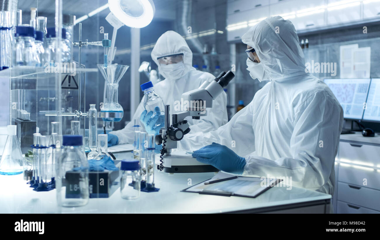 En un laboratorio de alto nivel seguro científicos en un sobretodo llevando a cabo una investigación. Ajusta químico de muestras y discutir el experimento con el colega. Imagen De Stock
