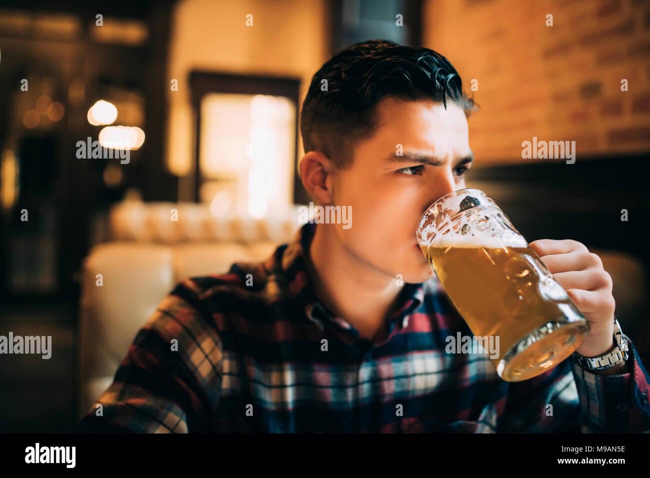 Hombre bebiendo cerveza. Joven bebiendo cerveza mientras está sentado en el mostrador de bar Imagen De Stock
