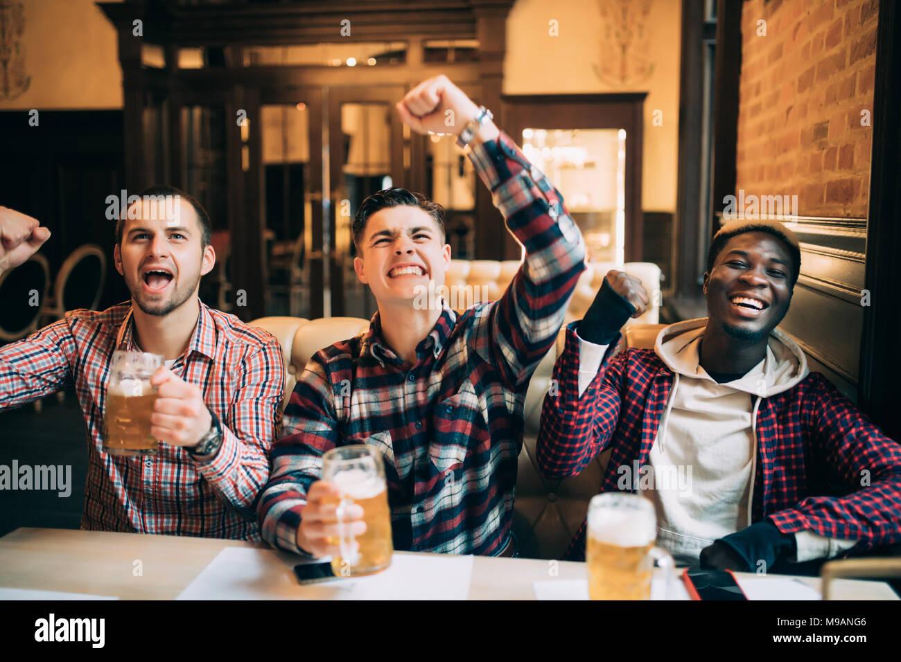 Feliz football fans o amigos varones bebiendo cerveza y celebrando la victoria en el bar o pub Imagen De Stock