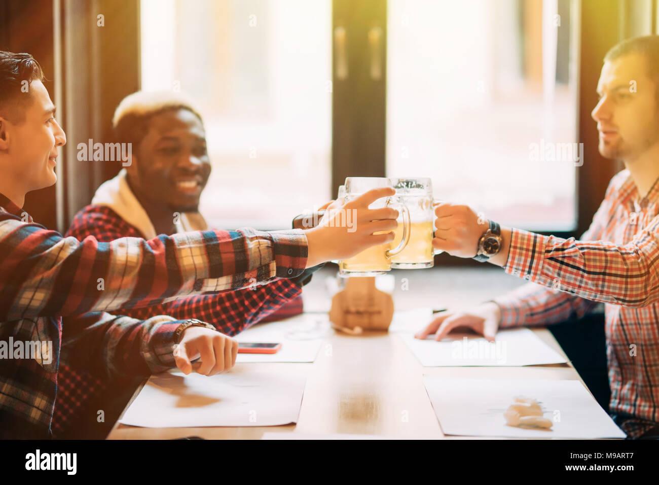 La gente, los hombres, el ocio, la amistad y la celebración concepto - feliz amigos varones bebiendo cerveza y vasos tintineo en el bar o pub Imagen De Stock