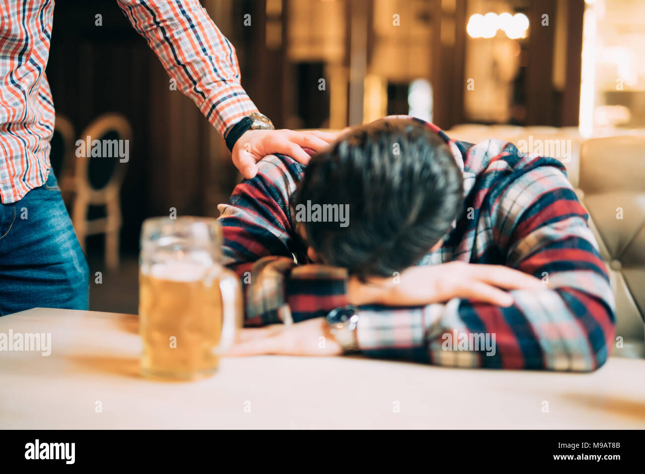 La gente, el ocio, la amistad y el concepto de partido - Hombre con cerveza despertando a su amigo borracho durmiendo sobre la mesa en el bar o pub Imagen De Stock