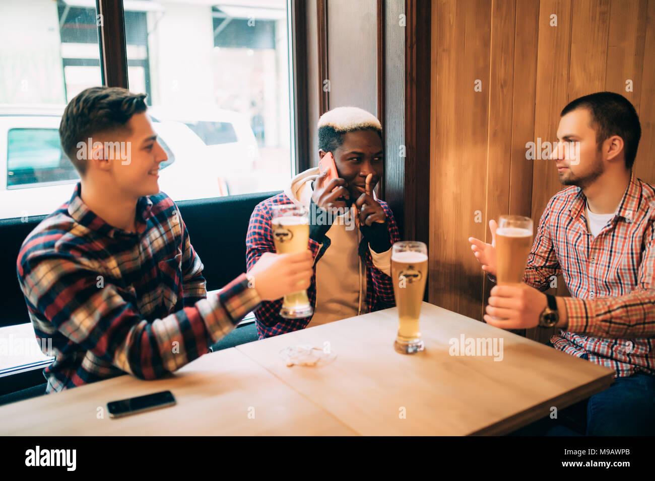 Dos amigos varones en bares están bebiendo cerveza y comunicarse mientras uno está hablando por teléfono y pidiendo silencio. Imagen De Stock