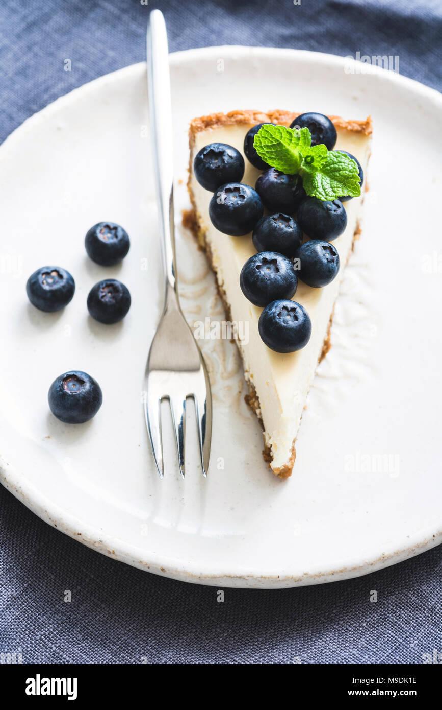 Tarta de queso con arándanos frescos en la placa blanca, el enfoque selectivo, composición vertical Imagen De Stock