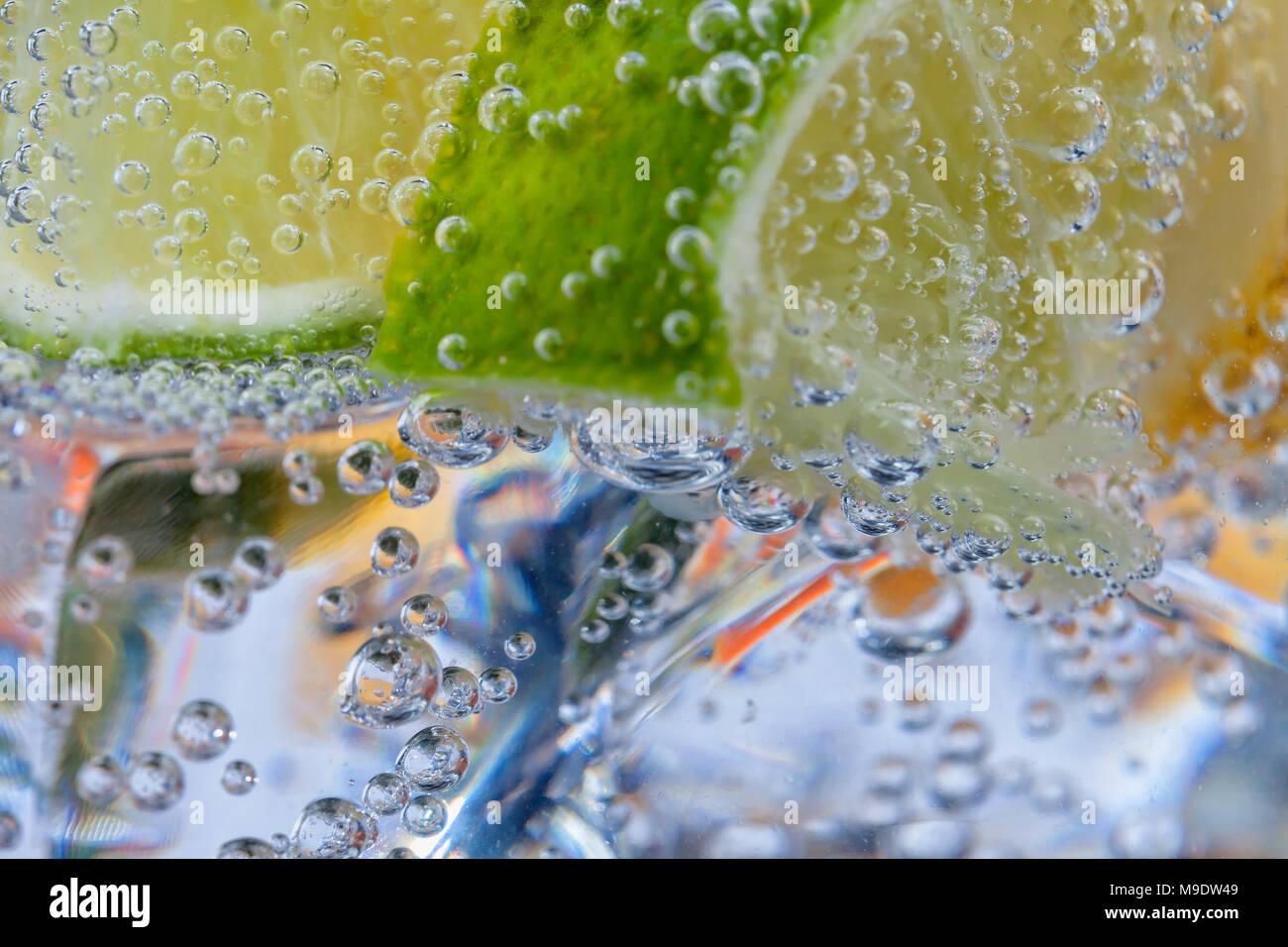 Cócteles caseros con cítricos en un vaso con bebida transparente ices y burbujas. Foto de stock