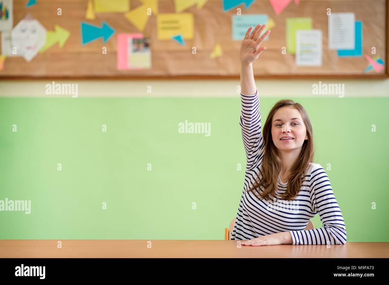 La educación, la escuela, el aprendizaje y el concepto de los adolescentes. Estudiante sentado en el aula y levantando la mano. Imagen De Stock