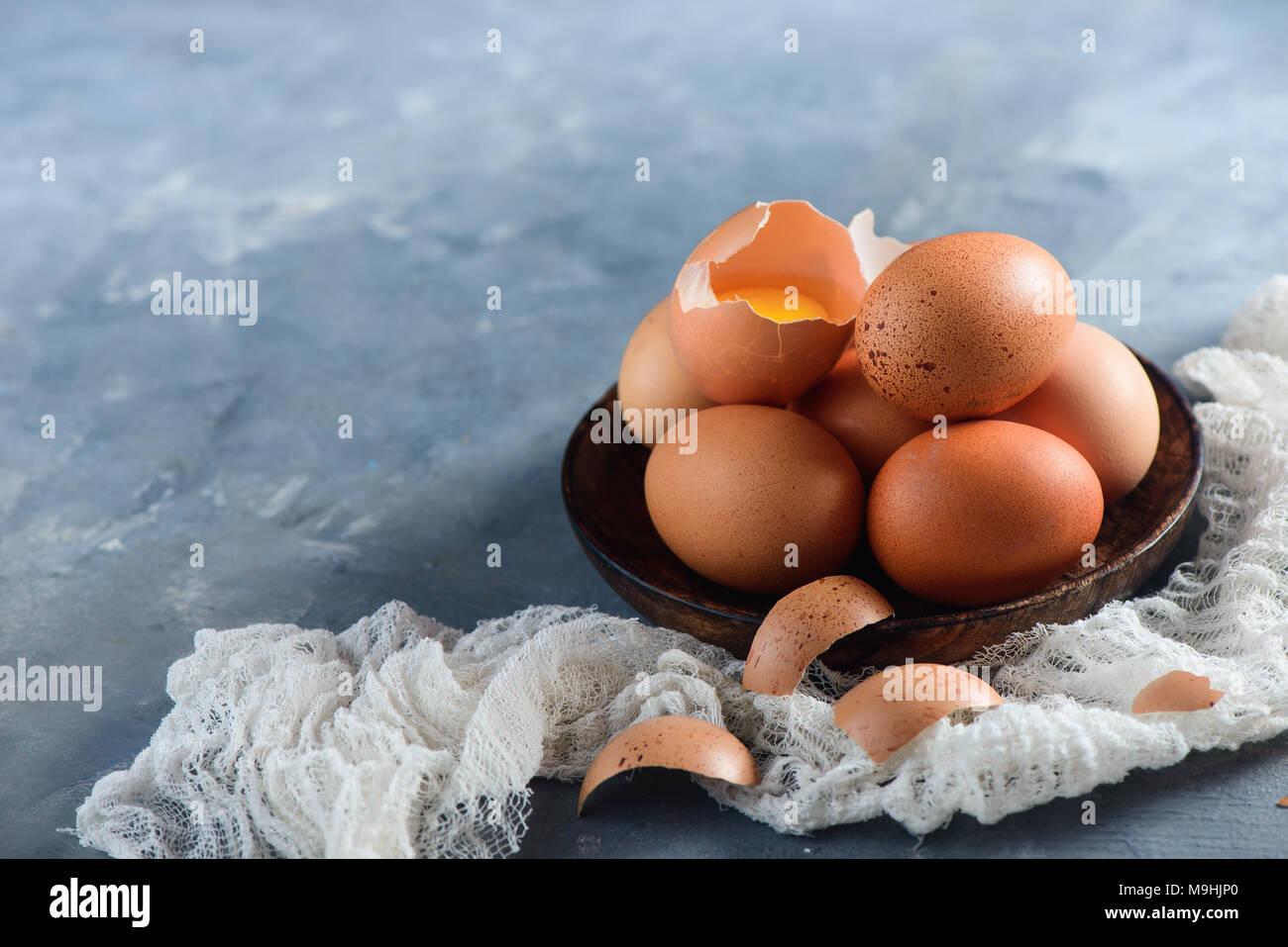 Los huevos de pollo fresco en un recipiente de madera sobre un fondo de hormigón con un paño blanco. Concepto de ingredientes orgánicos con espacio de copia. Imagen De Stock