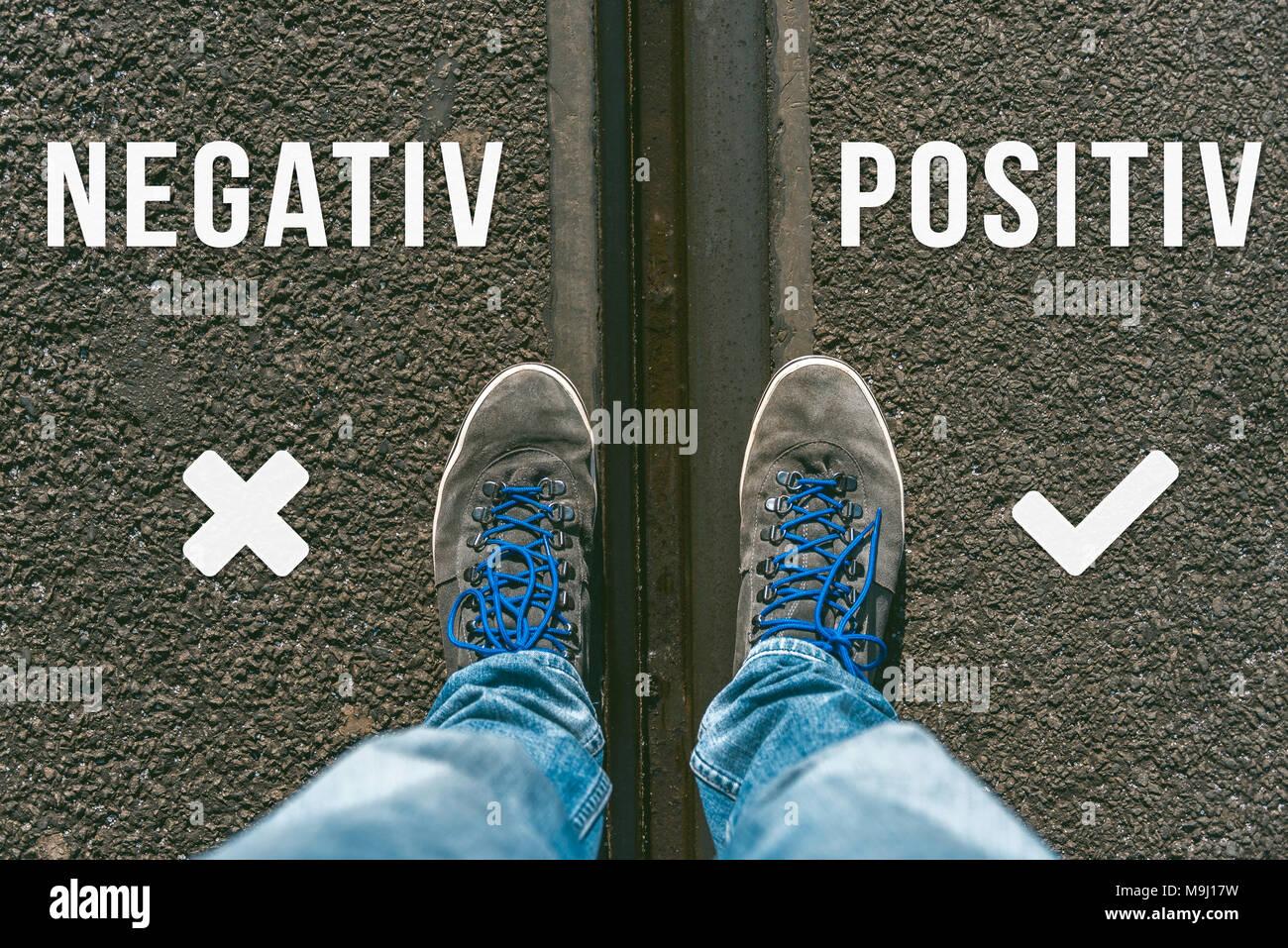 Llegando a una encrucijada de tener que decidir entre negativ y positiv en alemán significado negativo y positivo, simbolizados por dos pies y zapatos o permanente Imagen De Stock
