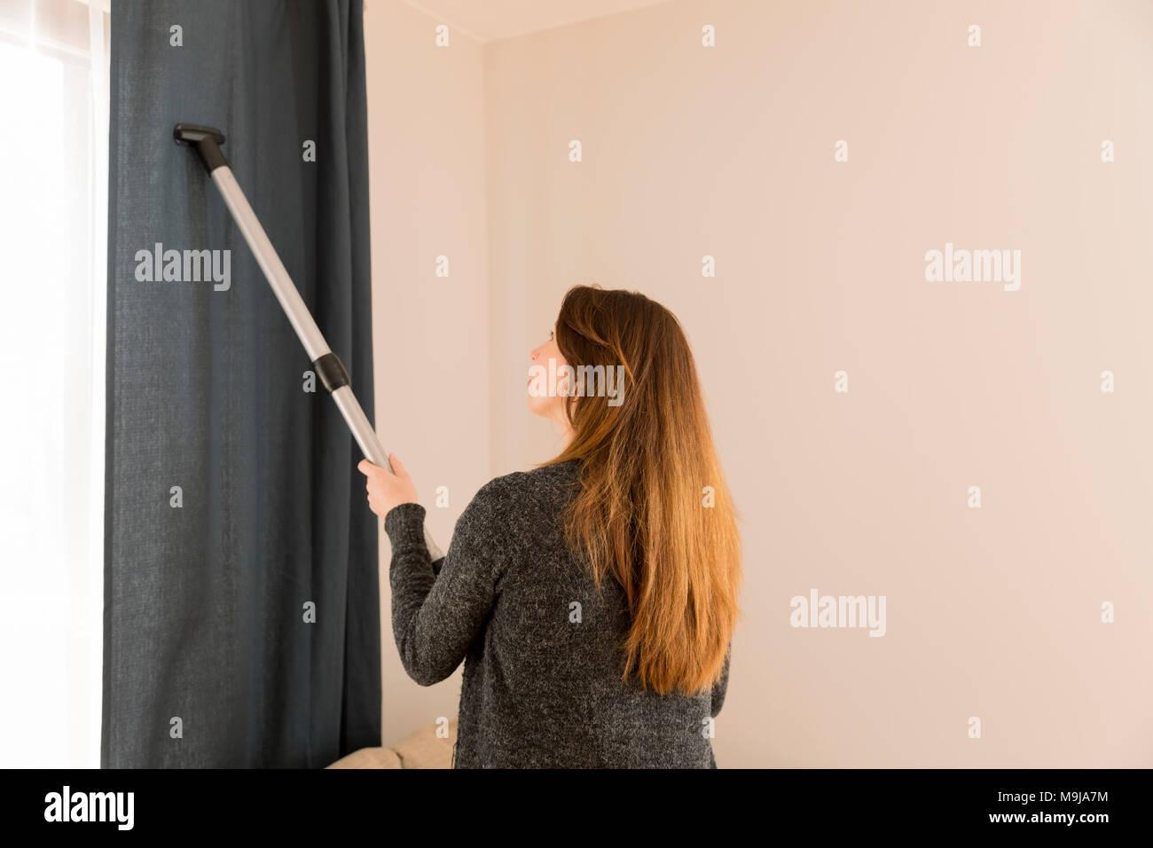 La gente, la casa y el concepto de limpieza - Mujer con aspirador en casa. Limpieza de cortina. Limpieza de Primavera Imagen De Stock