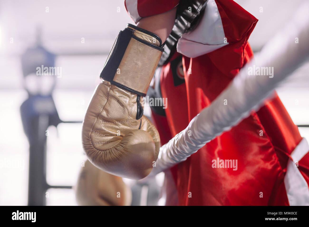 Vista lateral de la filmación en rojo sportswoman sportswear colgando su amarillo guantes de boxeo de la cuerda del anillo. batalla perdida. atados fighter Imagen De Stock