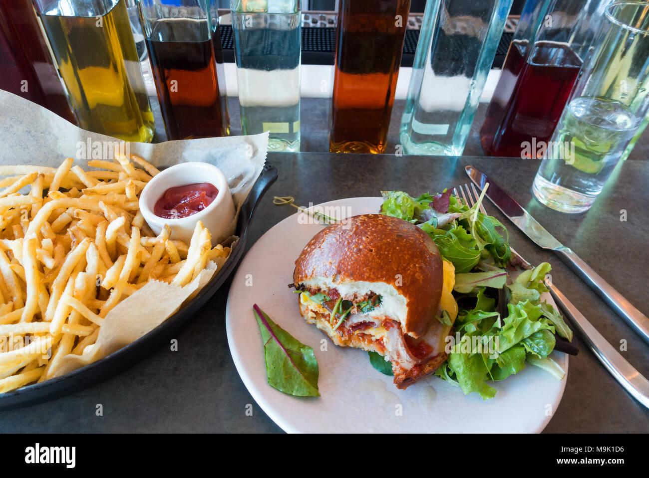 Huevos y bacon sandwich tostado suave en un rollo con ensalada de verduras mixtas Imagen De Stock