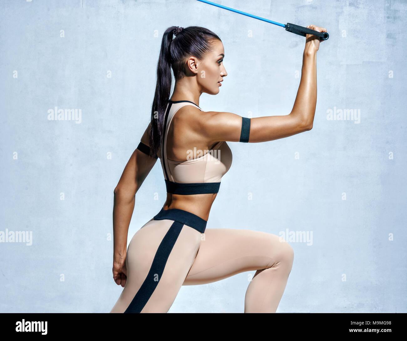 Mujer fuerte mediante la resistencia de banda en su rutina de ejercicio. Foto del modelo fitness entrenamiento sobre fondo gris. Fuerza y motivación Imagen De Stock