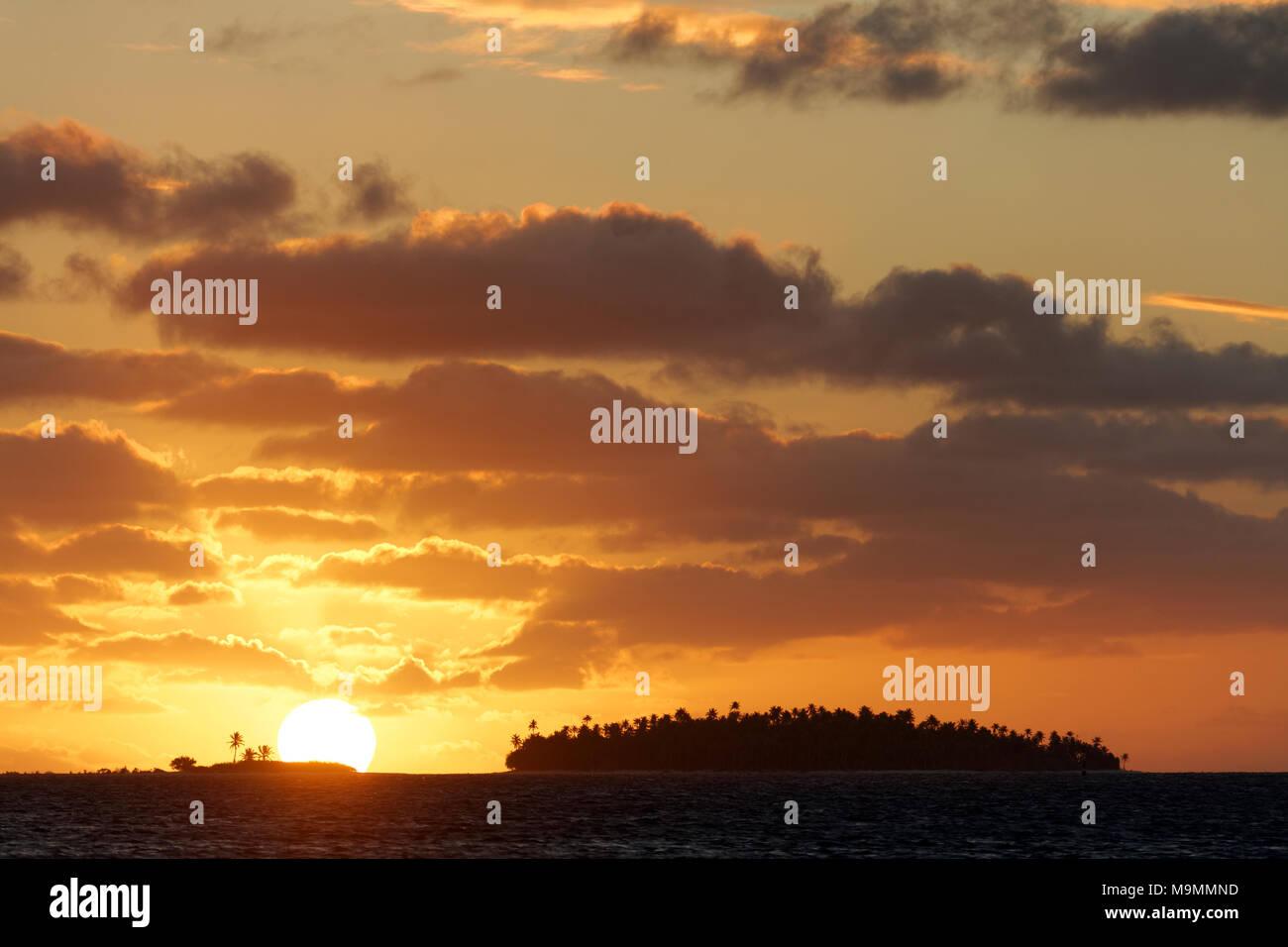 Sunset Island, cielo nuboso, Tikehau Atolón Archipiélago Tuamotu, Islas Sociedad, Polinesia Francesa, las islas de Barlovento Foto de stock