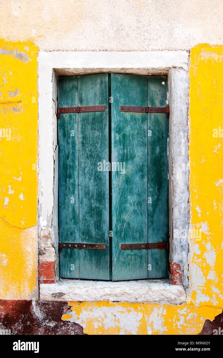 Ventana de madera antigua y pared amarilla de una casa en la isla de Burano, cerca de Venecia, Italia, Europa Imagen De Stock