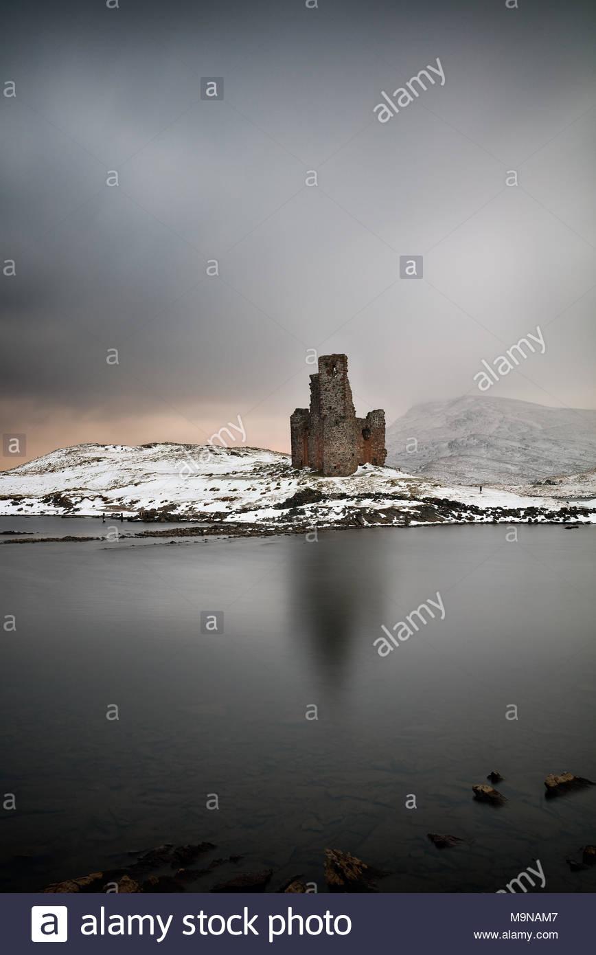 Una larga exposición de Ardvreck Castillo y montañas cubiertas de nieve en un paisaje invernal. Loch Assynt, Escocia. Foto de stock