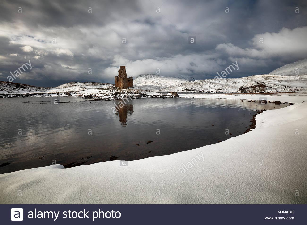 El castillo de Ardvreck y montañas cubiertas de nieve en un paisaje invernal. Loch Assynt, Escocia. Foto de stock