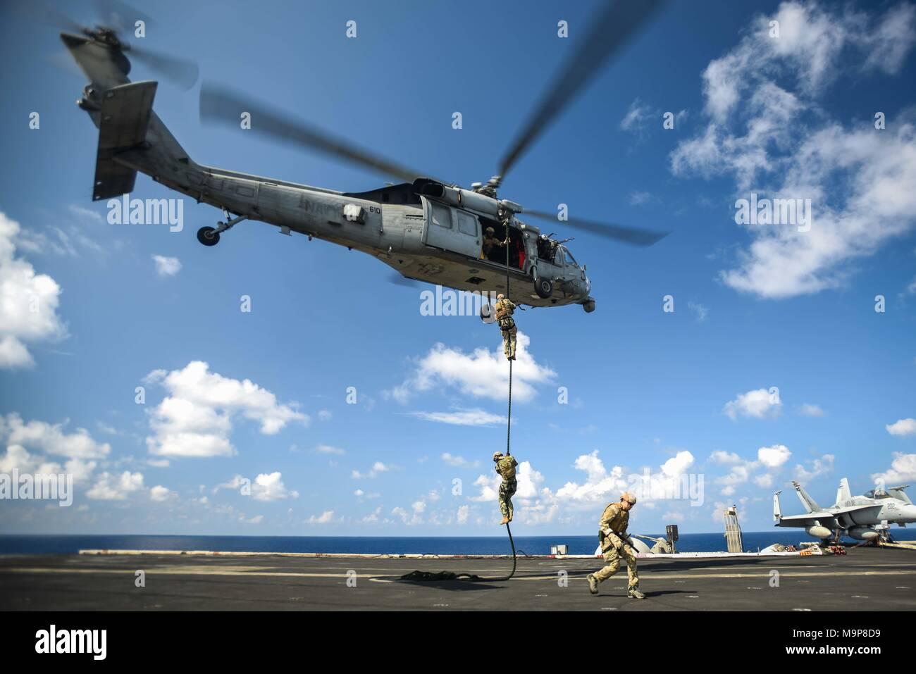 180327-N-VN584-2964 OCÉANO ÍNDICO (27 de marzo de 2018) Los marineros, asignado a la eliminación de Artefactos Explosivos unidad móvil (EODMU) 1, fast rope desde un MH-60S Sea Hawk, asignado a los indios del escuadrón de helicópteros de combate de mar (HSC) 6, en la cubierta de vuelo del portaaviones USS Theodore Roosevelt (CVN 71). Theodore Roosevelt está actualmente en curso de un despliegue programado regularmente en los EE.UU. 7ª zona de operaciones de la flota en apoyo de operaciones de seguridad marítima y los esfuerzos de cooperación de seguridad de teatro. (Ee.Uu. Navy photo by Mass Communication Specialist 3ª clase Alex Corona/liberado) Imagen De Stock
