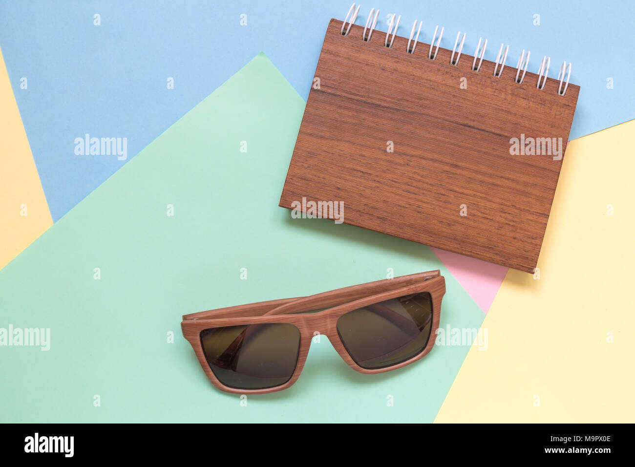 El bloc de notas de madera y unas gafas de sol de color Mínima de ...