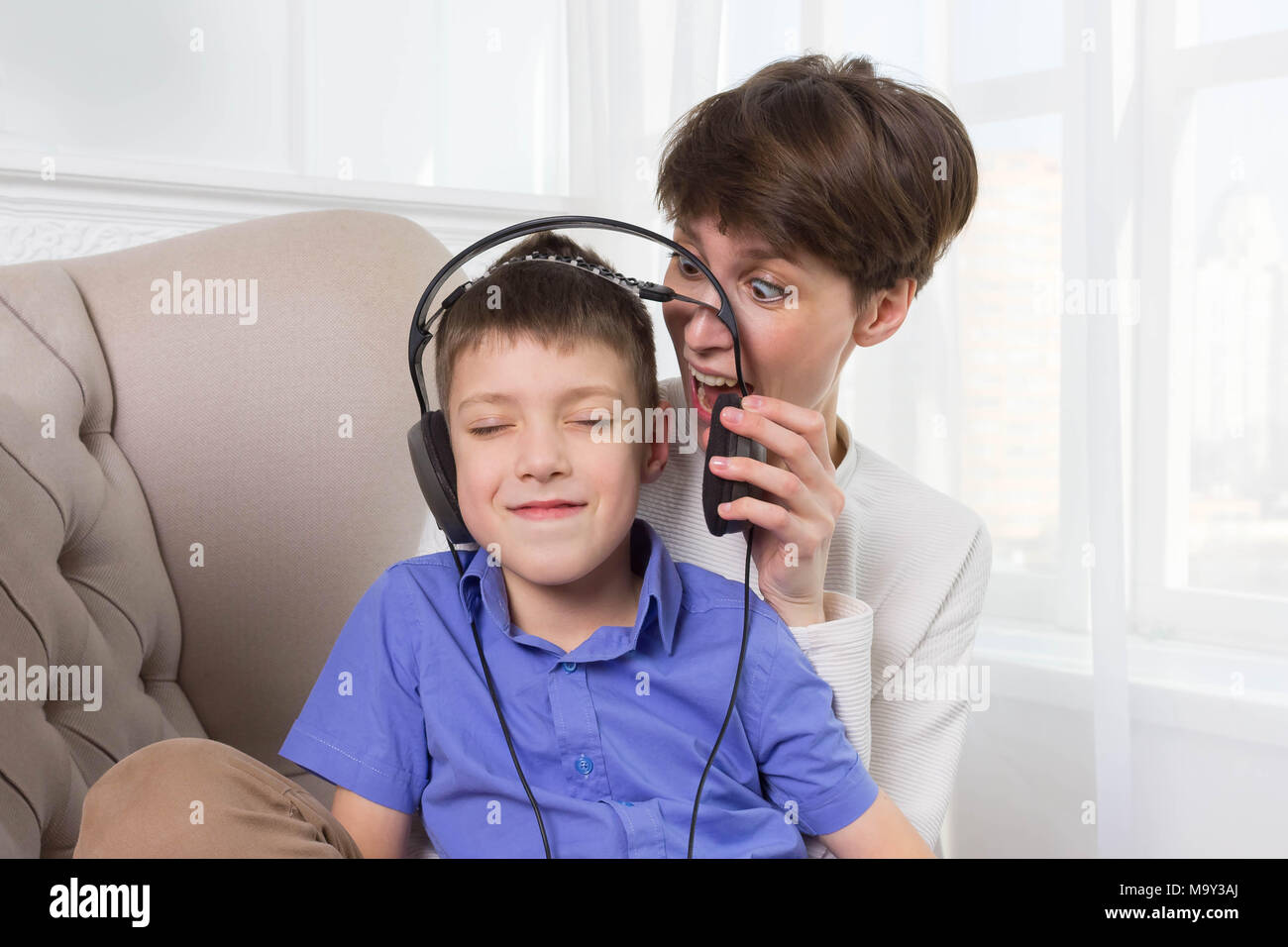 Madre gritando a su hijo mientras él escuchando música y no escuchar Imagen De Stock