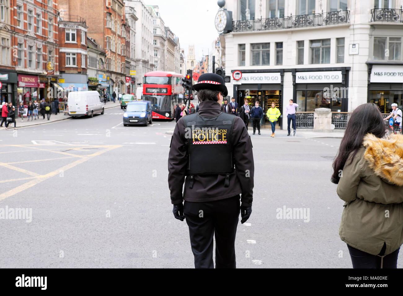 Vista posterior de la mujer policía femenina de la ciudad de Londres en uniforme de policía en la calle en el centro de Londres, Inglaterra Gran Bretaña KATHY DEWITT Imagen De Stock