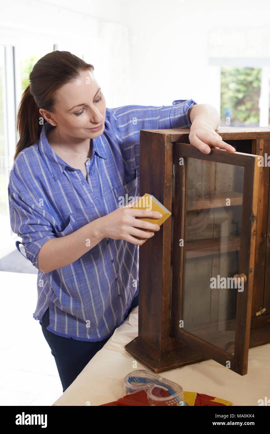 Mujer Upcycling Gabinete de madera en casa Imagen De Stock