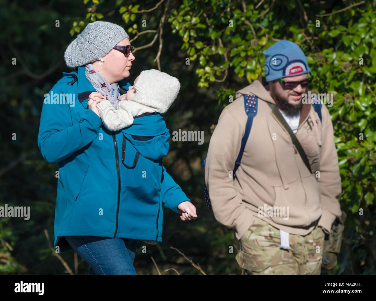 Una pareja caminando en invierno con la mujer que llevaba a un bebé en un soporte conectado a su frente. Mantener al niño cerca. Imagen De Stock