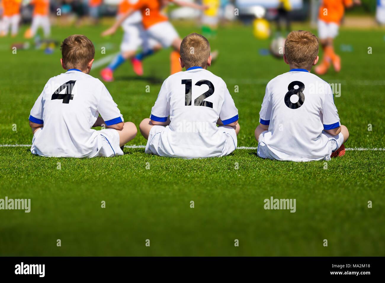 591721787ba0f Entrenamiento de fútbol juvenil. Los muchachos sentados en campo de fútbol  y Ver juego de torneo. Partido de fútbol para niños