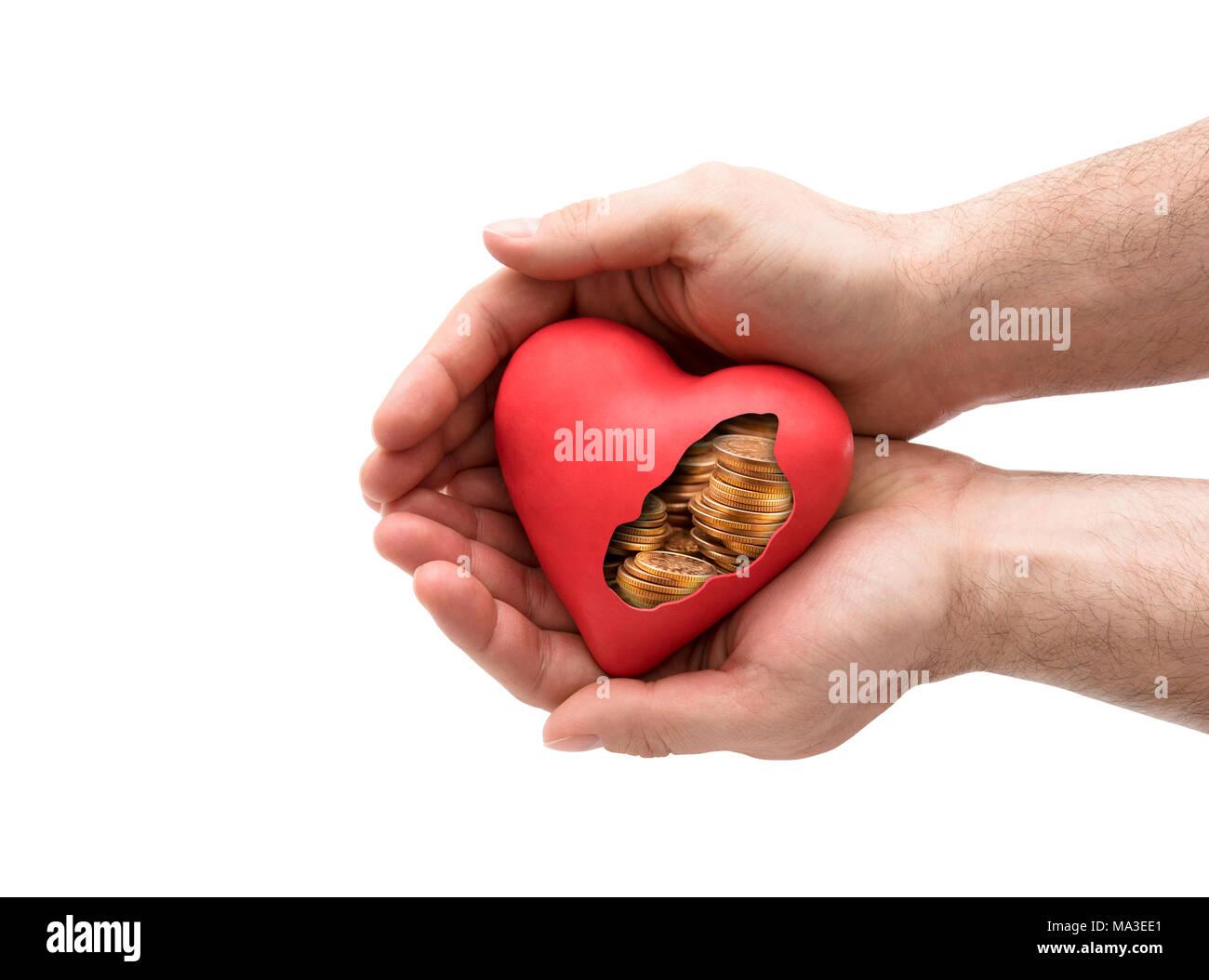 Corazón rojo con monedas de oro en manos sobre fondo blanco con trazado de recorte Imagen De Stock