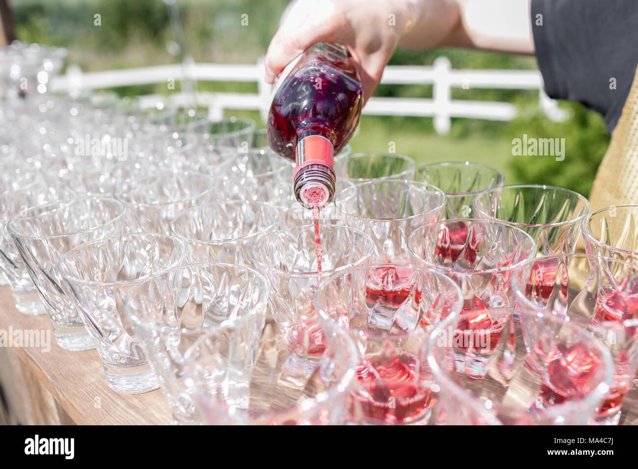 Manos de un camarero que hace pirámide de vasos para bebidas, vino, champagne, ambiente festivo, de celebración Imagen De Stock
