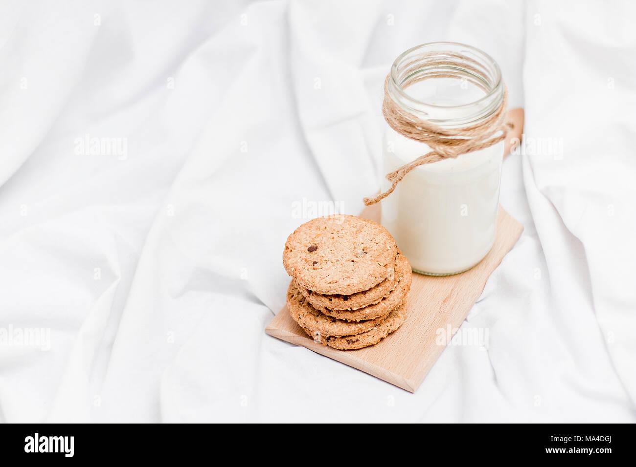 Foto de una jarra de leche y galletas sobre una tabla de madera sobre una hoja de cama Foto de stock