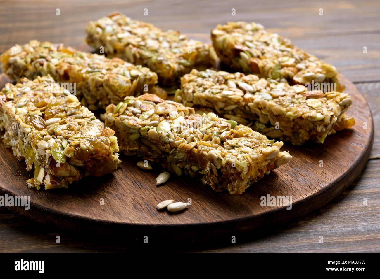 Barra de granola. Snack saludable de energía sobre la plancha de madera. Vista cercana Imagen De Stock