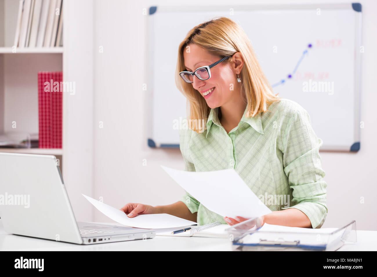 Feliz empresaria está trabajando en su oficina. Imagen De Stock
