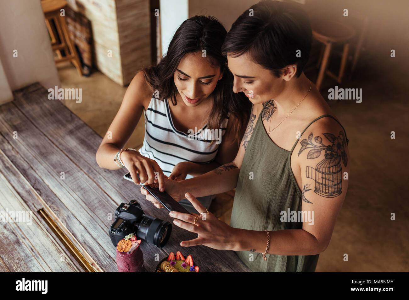 Las mujeres bloggers fotografías de cuenco de fruta y batidos jar colocado junto con una cámara DSLR para un artículo de blog de alimentos. Los bloggers de alimentos busca en th Imagen De Stock