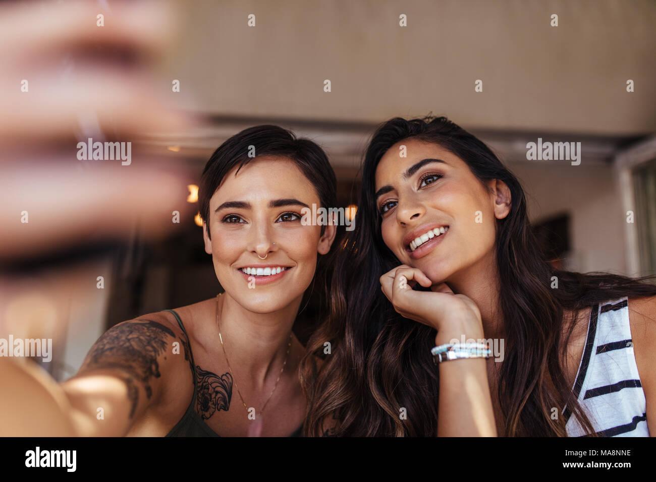 Dos mujeres sentadas afuera mirando un teléfono móvil. Mujer sonriente posando para un selfie. Imagen De Stock
