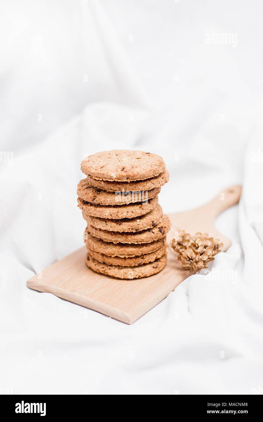 Galletas caseras dulce sobre una tabla de madera y fondo blanco. Imagen De Stock