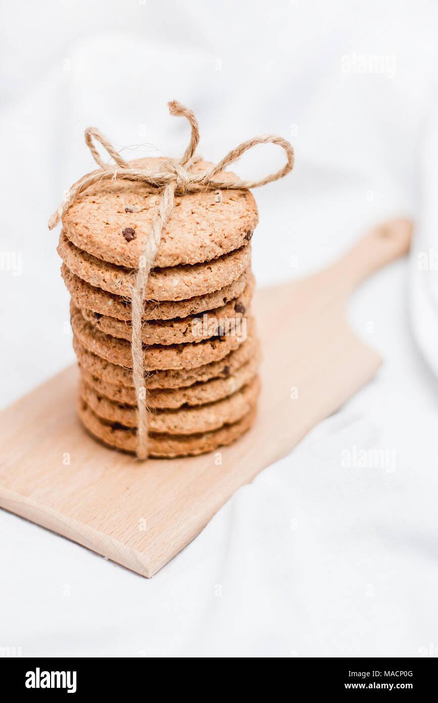 Galletas caseras dulces envueltos con cuerda sobre una tabla de madera y fondo blanco. Imagen De Stock