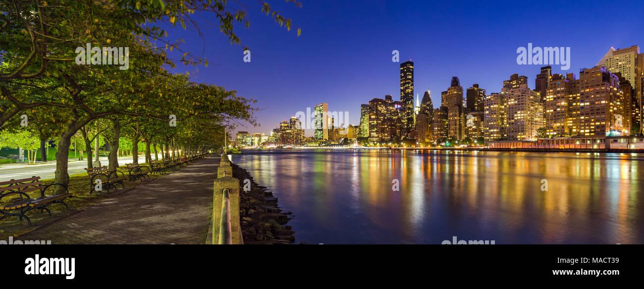 Vistas panorámicas de los rascacielos de Manhattan y el East River en la penumbra de Roosevelt Island paseo en verano. La Ciudad de Nueva York Imagen De Stock