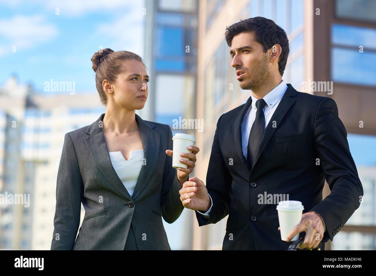 Joven agente de seguros en traje explicando su colega cómo hacer el siguiente paso en su negocio durante la piscina coffee-break Foto de stock