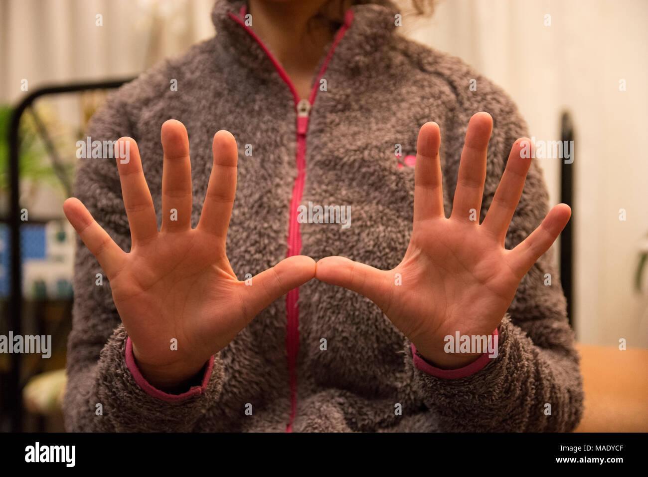 Una mujer mantenga sus manos colocadas simétricamente en la parte frontal de la cámara. Imagen De Stock