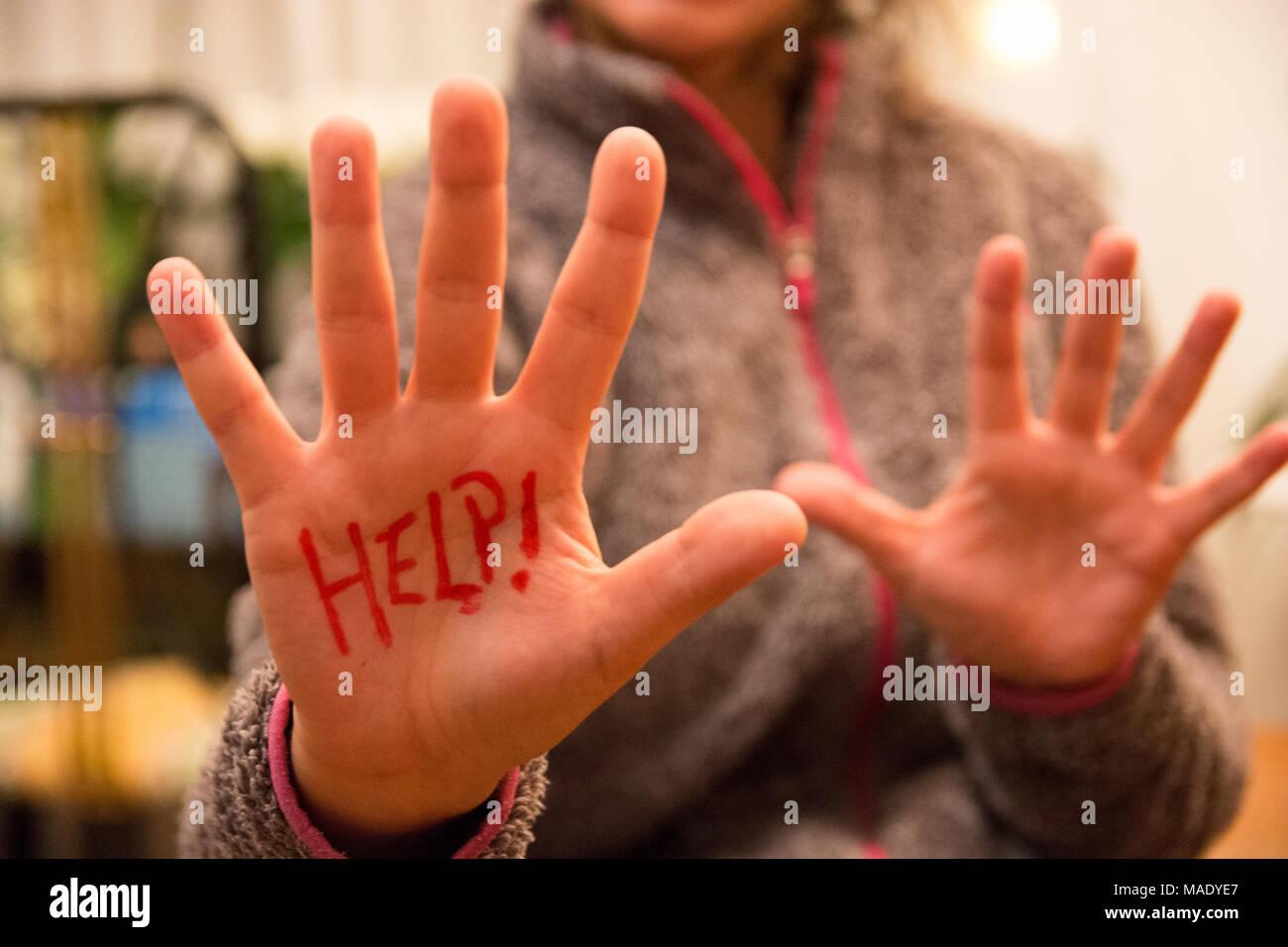 Ayuda! Escrito en mujer mano cerca de la cámara. La mujer pide ayuda escribiendo en su mano. Imagen De Stock